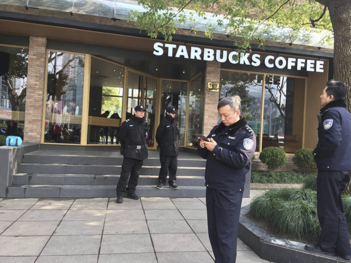 Police officers stand outside of a Starbucks cafe near the site where a minivan carrying gas tanks plowed into pedestrians in Shanghai, Friday, Feb. 2, 2018. A minivan plowed into pedestrians on a sidewalk in downtown Shanghai on Friday, sending more than a dozen people to hospitals. (AP Photo)