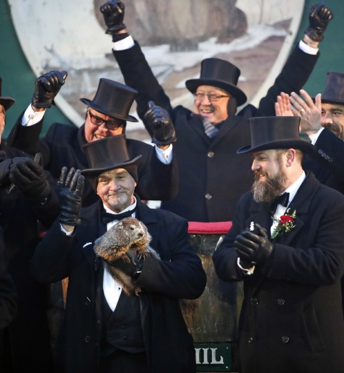 Groundhog Club co-handler John Griffiths co-handler, left front, holds Punxsutawney Phil, the weather prognosticating groundhog, during the 132nd celebration of Groundhog Day on Gobbler's Knob in Punxsutawney, Pa. Friday, Feb. 2, 2018. Phil's handlers said that the groundhog has forecast six more weeks of winter weather. (AP Photo/Gene J. Puskar)