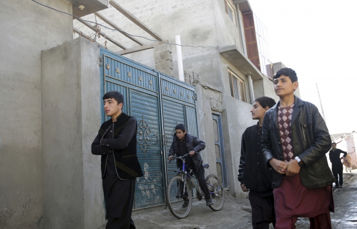 Residents walk pass the house in which Islamic State insurgents were hidden, in a street of Qala-e-Walid neighborhood in Kabul, Afghanistan, Friday, Feb. 2, 2018. The Afghan authorities found an Islamic State hideout packed with explosives in a poor western neighborhood of the capital where residents of the area say they rarely see a police patrol, and marauding bands of thieves makes it unsafe to be on the streets after dark. (AP Photo/Massoud Hossaini)