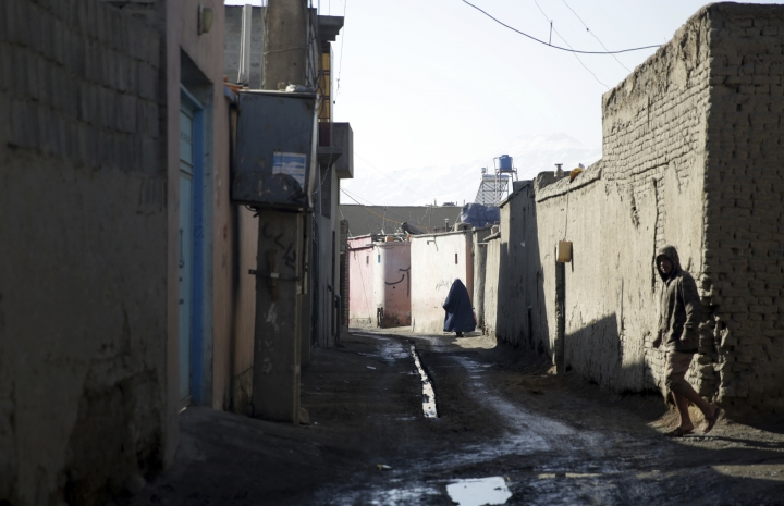 A young man walks pass a street of Qala-e-Walid neighborhood in Kabul, Afghanistan, Friday, Feb. 2, 2018. The Afghan authorities found an Islamic State hideout packed with explosives in a poor western neighborhood of the capital where residents of the area say they rarely see a police patrol, and marauding bands of thieves makes it unsafe to be on the streets after dark. (AP Photo/Massoud Hossaini)