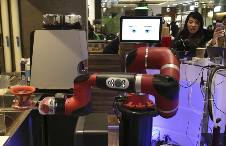 """Robot barista named """"Sawyer"""" makes a coffee at Henn-na Cafe, Japanese meaning """"Strange Cafe""""in Tokyo, Friday, Feb. 2, 2018. The cafe's robot barista brews and serves coffee as the rapidly aging country seeks to adapt to shrinking workforce. The arm robot """"Sawyer"""" debuted this week in Tokyo's downtown business and shopping district of Shibuya. (AP Photo/Koji Sasahara)"""
