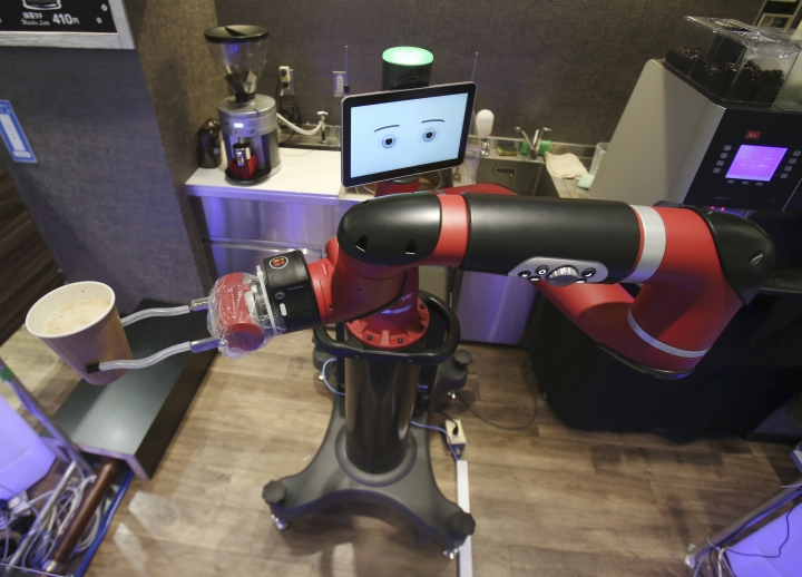"""Robot barista named """"Sawyer"""" makes a coffee at Henn-na Cafe, meaning """"Strange Cafe"""" in Japanese, in Tokyo, Friday, Feb. 2, 2018. The cafe's robot barista brews and serves coffee as the rapidly aging country seeks to adapt to shrinking workforce. The arm robot """"Sawyer"""" debuted this week in Tokyo's downtown business and shopping district of Shibuya. (AP Photo/Koji Sasahara)"""