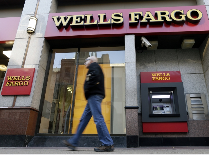 FILE - In this Wednesday, Dec. 19, 2012, file photo, a man walks past a Wells Fargo location in Philadelphia. The Federal Reserve is imposing more penalties on Wells Fargo, freezing the bank's growth until it can prove it has improved its internal controls. The new penalties were announced late Friday, Feb. 2, 2018, on Fed Chair Janet Yellen's last day at the central bank. (AP Photo/Matt Rourke, File)