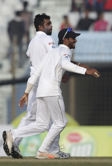 Sri Lanka's Dilruwan Perera, left, celebrates with his teammate Dhananjaya de Silva the dismissal of Bangladesh's Imrul Kayes during the fourth day of their first test cricket match in Chittagong, Bangladesh, Saturday, Feb. 3, 2018. (AP Photo/A.M. Ahad)
