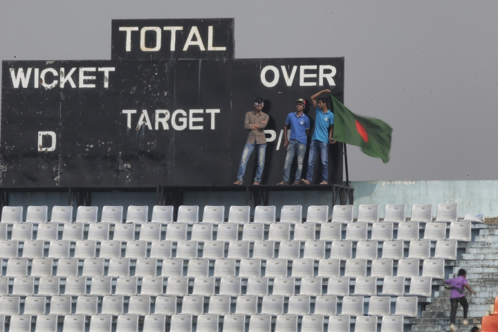A Bangladeshi spectator holds a National flag, as they watch the match during the fourth day of the first test cricket match between Bangladesh and Sri Lanka in Chittagong, Bangladesh, Saturday, Feb. 3, 2018. (AP Photo/A.M. Ahad)