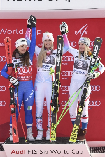 From left, second placed Italy's Sofia Goggia, first placed United States' Lindsey Vonn and third placed Austria's Cornelia Huetter celebrate on the podium at the end of an alpine ski, women's world Cup downhill race, in Garmisch Partenkirchen, Germany, Saturday, Feb. 3, 2018. (AP Photo/Marco Tacca)