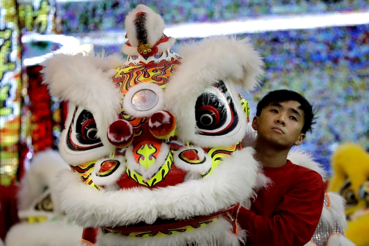 CORRECTS TO TROUPE - In this Friday, Feb. 2, 2018, photo, a member of a lion dance troupe from Hong Kong waits to compete in the 11th International Lion Dance Competition in Singapore. This lion dace competition is usually held in a lead up to the Chinese Lunar New Year celebrated in Singapore. Lion dance is a traditional dance in Chinese culture and some other Asian countries in which performers from a lion dance troupe will mimic a lion's movements while dressed in a lion's costume. This is believed to bring fortune and luck. These performers from Vietnam, Singapore, Myanmar, Indonesia, Hong Kong, Taiwan and Malaysia gathered in Singapore to compete against one another and are judged on their skill, grace and musicality amongst other things. (AP Photo/Wong Maye-E)