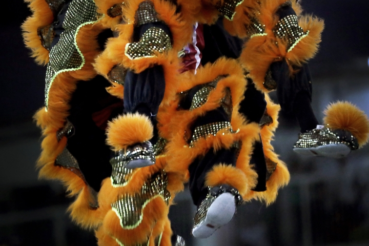 CORRECTS TO TROUPE - In this Friday, Feb. 2, 2018, photo, members of a lion dance troupe in Singapore are airborne as they compete in the 11th International Lion Dance Competition in Singapore. This lion dace competition is usually held in a lead up to the Chinese Lunar New Year celebrated in Singapore. Lion dance is a traditional dance in Chinese culture and some other Asian countries in which performers from a lion dance troupe will mimic a lion's movements while dressed in a lion's costume. This is believed to bring fortune and luck. These performers from Vietnam, Singapore, Myanmar, Indonesia, Hong Kong, Taiwan and Malaysia gathered in Singapore to compete against one another and are judged on their skill, grace and musicality amongst other things. (AP Photo/Wong Maye-E)