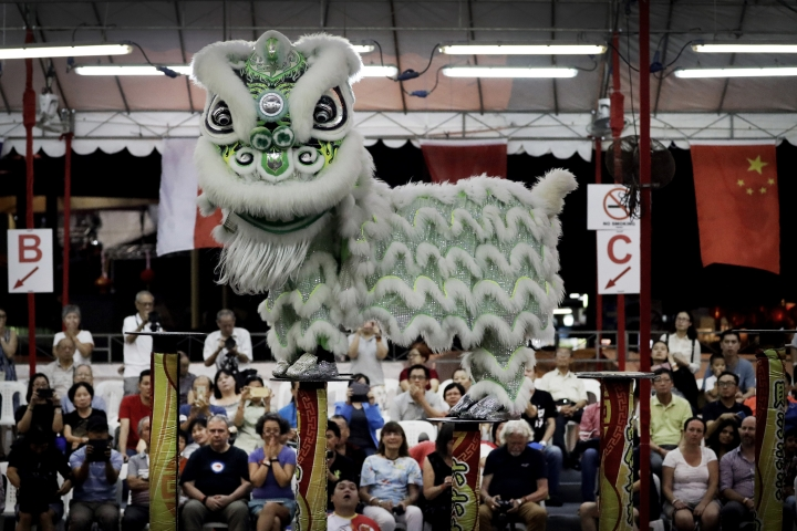 CORRECTS TO TROUPE - In this Friday, Feb. 2, 2018, photo, spectators watch as members of a lion dance troupe from Indonesia compete in the 11th International Lion Dance Competition in Singapore. This lion dace competition is usually held in a lead up to the Chinese Lunar New Year celebrated in Singapore. Lion dance is a traditional dance in Chinese culture and some other Asian countries in which performers from a lion dance troupe will mimic a lion's movements while dressed in a lion's costume. This is believed to bring fortune and luck. These performers from Vietnam, Singapore, Myanmar, Indonesia, Hong Kong, Taiwan and Malaysia gathered in Singapore to compete against one another and are judged on their skill, grace and musicality amongst other things. (AP Photo/Wong Maye-E)
