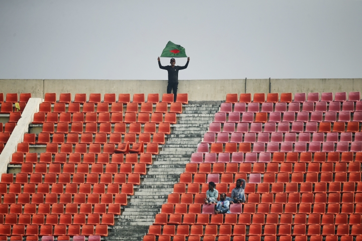 A Bangladeshi spectator holds a National flag during the fifth and final day of the first test cricket match between Bangladesh and Sri Lanka in Chittagong, Bangladesh, Sunday, Feb. 4, 2018. (AP Photo/A.M. Ahad)