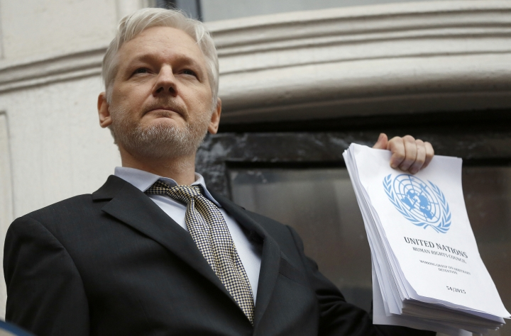 FILE - This is a Friday, Feb. 5, 2016 file photo of WikiLeaks founder Julian Assange holds a U.N. report as he speaks on the balcony of the Ecuadorian Embassy in London. A British judge is scheduled to rule on Tuesday Feb. 6, 2017 on Julian Assange's bid to force Britain to drop a warrant for his arrest, a development that would remove a substantial legal hurdle to his leaving the Ecuadorean Embassy in London that has been his refuge for more than five years. Here is a look at the legal issues surrounding the complex case of the WikiLeaks founder. (AP Photo/Frank Augstein, File)
