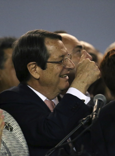 Cyprus President Nicos Anastasiades waves to supporters who gathered at a stadium to attend his inauguration ceremony after being re-elected to a second five-year term in Nicosia, Sunday, Feb. 4, 2018. Anastasiades defeated challenger Stravros Malas, who was supported by the communist-rooted AKEL party, by a wide margin. (AP Photo/Petros Karadjias)