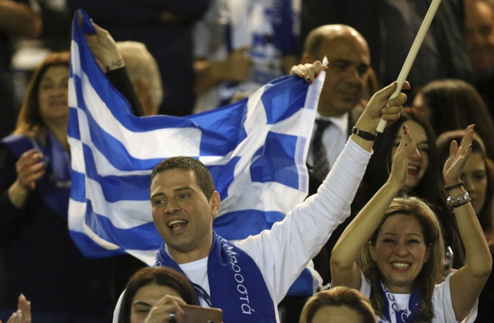Supporters of Cyprus President Nicos Anastasiades who gathered at a stadium to attend his inauguration ceremony wave Greek flags in Nicosia, Sunday, Feb. 4, 2018. Anastasiades was re-elected by a wide margin after defeating left-leaning challenger Stavros Malas in a runoff election for the second time in a row. (AP Photo/Petros Karadjias)