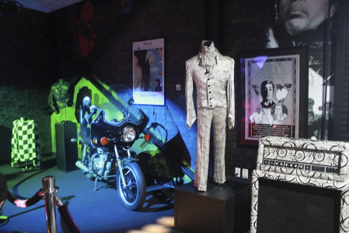 "FILE - In this Nov. 2, 2016 file photo, a Prince costume and motorcycle are on display at Prince's Paisley Park in Chanhassen, Minn. Julien's Auctions announced Monday, Feb. 5, 2018 that ruffled, sparkly outfits worn by Prince and one of his famous white ""Cloud"" guitars are among memorabilia up for auction May 18, in New York. (AP Photo/Jeff Baenen, File)"
