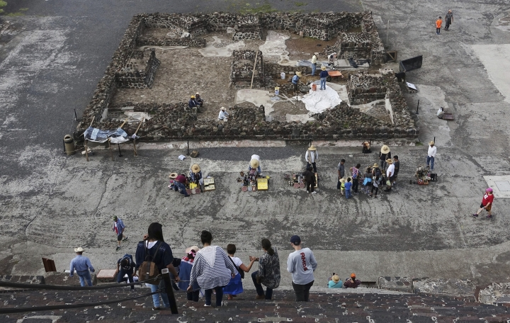 In this July 27, 2016 photo, with archaeology work going on in the background, tourists descend the Pyramid of the Moon at the ruins of Teotihuacan in Teotihuacan, Mexico. (AP Photo/Ross D. Franklin)