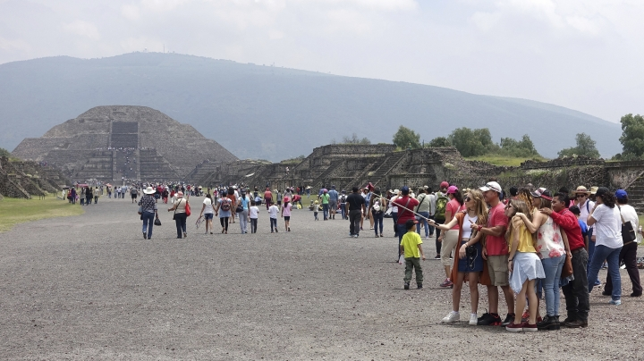 In this July 27, 2016 photo, tourists walk and pose for pictures on the Avenue of The Dead as the Pyramid of The Moon looms in the background at the ruins of Teotihuacan in Teotihuacan, Mexico. (AP Photo/Ross D. Franklin)