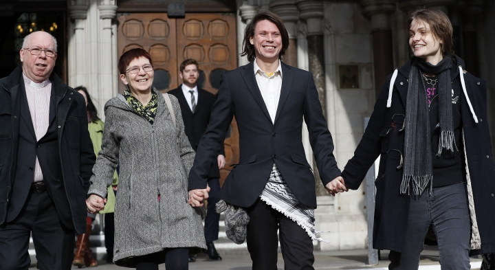 Lauri Love smiles as he leaves with parents Alexander Love, left, Sirkka-Liisa Love, second left, and girlfriend Sylvia Mann, from The Royal Courts of Justice in London, Monday, Feb. 5, 2018. The ruling in Lauri Love's appeal against extradition to the United States, where he faced solitary confinement and a potential 99 year prison sentence, was ruled in his favour on Monday Feb. 5 at the Royal Courts of Justice. (AP Photo/Kirsty Wigglesworth)