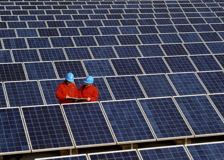 FILE - In this Feb. 7, 2012, file photo, workers check solar panels at a solar power station on a factory roof in Changxing in eastern China's Zhejiang province. One of China's biggest makers of solar panels said Tuesday, Feb. 6, 2018, that it will invest $309 million to expand manufacturing in India to guard against what it said is a rising threat of import controls in the United States and other markets. (Chinatopix via AP, File)