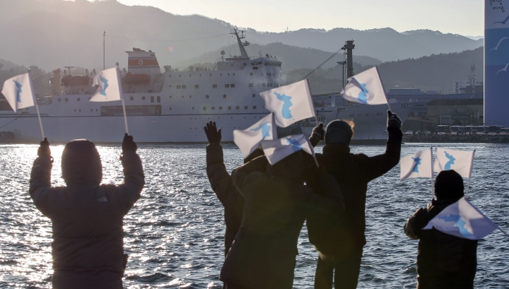 South Koreans wave unification flags as North Korea's Mangyongbong-92 ferry carrying North Korea's members of art troupe approaching to Mukho Port in Donghae, South Korea, Tuesday, Feb. 6, 2018. The art troupe, led by Hyon Song Wol, also the leader of the famous Moranbong girl band hand-picked by North Korean leader Kim Jong Un, will perform in Gangneung and Seoul on Feb. 8 and Feb. 11, respectively, before returning home. (Kim Do-hoon/Yonhap via AP)