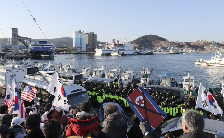 Members of conservative civic groups stage a protest against North Korea as North Korea's Mangyongbong-92 ferry, top center, carrying North Korea's members of art troupe approaching to Mukho Port in Donghae, South Korea, Tuesday, Feb. 6, 2018. The art troupe, led by Hyon Song Wol, also the leader of the famous Moranbong girl band hand-picked by North Korean leader Kim Jong Un, will perform in Gangneung and Seoul on Feb. 8 and Feb. 11, respectively, before returning home. (Yang Yong-suck/Yonhap via AP)