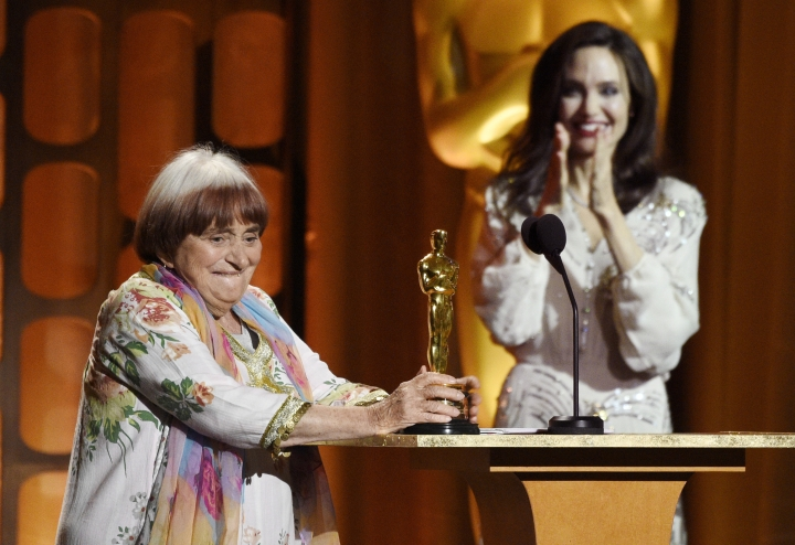 "FILE - In this Nov. 11, 2017 file photo, French film director Agnes Varda, left, accepts her honorary Oscar as presenter Angelina Jolie applauds at the 2017 Governors Awards in Los Angeles. Varda received an honorary Academy Award recognizing her decades of filmmaking. She also shares the documentary feature Oscar nomination for ""Faces Places"" with her co-director, JR, and her producer daughter, Rosalie Varda. (Photo by Chris Pizzello/Invision/AP, File)"