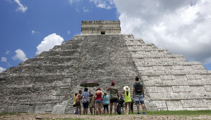 In this July 22, 2016 photo, tourists are dwarfed by El Castillo at the Chichen-Itza ruins in Yucatan, Mexico. While beach destinations remain popular for spring break, travel agents say customers are also demanding unique cultural experiences and active outdoorsy adventures. (AP Photo/Ross D. Franklin)