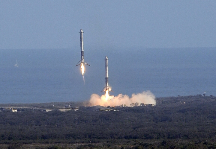 Two booster rockets from the Falcon 9 SpaceX heavy, return for a landing at the Kennedy Space Center in Cape Canaveral, Fla., Tuesday, Feb. 6, 2018. (AP Photo/John Raoux)