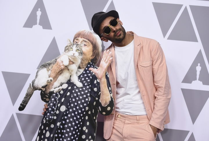 JR, right, poses with a cut-out of Agnes Varda as he arrive at the 90th Academy Awards Nominees Luncheon at The Beverly Hilton hotel on Monday, Feb. 5, 2018, in Beverly Hills, Calif. (Photo by Jordan Strauss/Invision/AP)