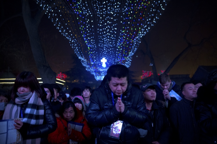 """FILE - In this Dec. 24, 2015 file photo, an overflow crowd prays outside of the Southern Cathedral, an officially-sanctioned Catholic church in Beijing, during a Christmas Eve mass. The retired archbishop of Hong Kong has slammed the Holy See's negotiations with the Chinese government as a """"catastrophe"""" that would bring suffering to millions of worshippers, as he escalates an extraordinary war of words against his church. (AP Photo/Mark Schiefelbein, File)"""