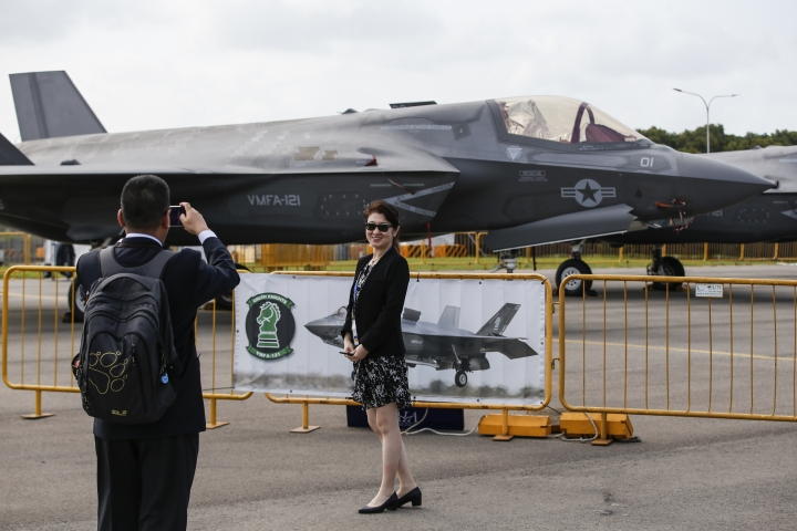 Visitors take a photo with an F-35B fighter jet parked at the static display area during the Singapore Airshow Wednesday, Feb. 7, 2018, in Singapore. (AP Photo/Yong Teck Lim)