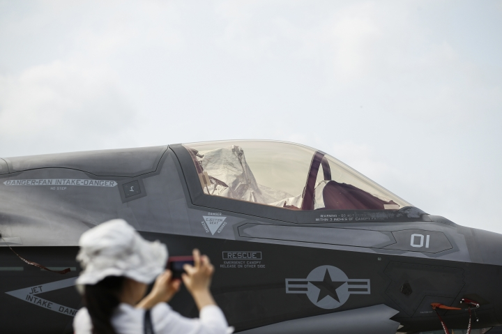 A visitor takes a photo of an F-35B fighter jet parked at the static display area during the Singapore Airshow on Wednesday, Feb. 7, 2018, in Singapore. (AP Photo/Yong Teck Lim)