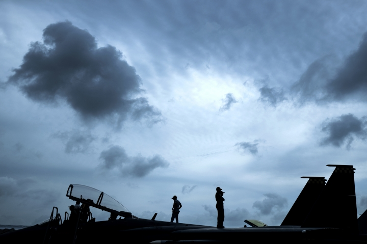 Republic of Singapore Air Force staff are silhouetted as they stand atop an F-15SG fighter jet during the Singapore Airshow on Wednesday, Feb. 7, 2018, in Singapore. (AP Photo/Yong Teck Lim)