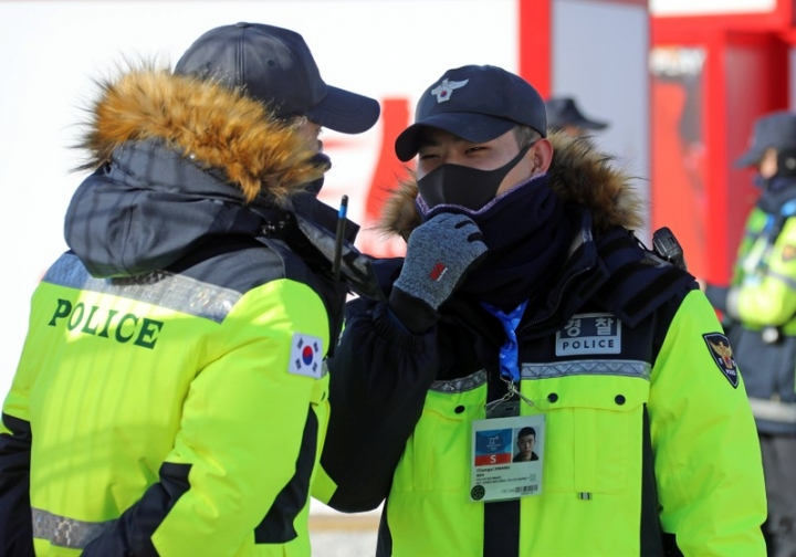 Two police officers protect their face from the cold at the Olympic stadium of the Pyeongchang Winter Olympic Games in Pyeongchang, South Korea February 7, 2018.     REUTERS/Eric Gaillard