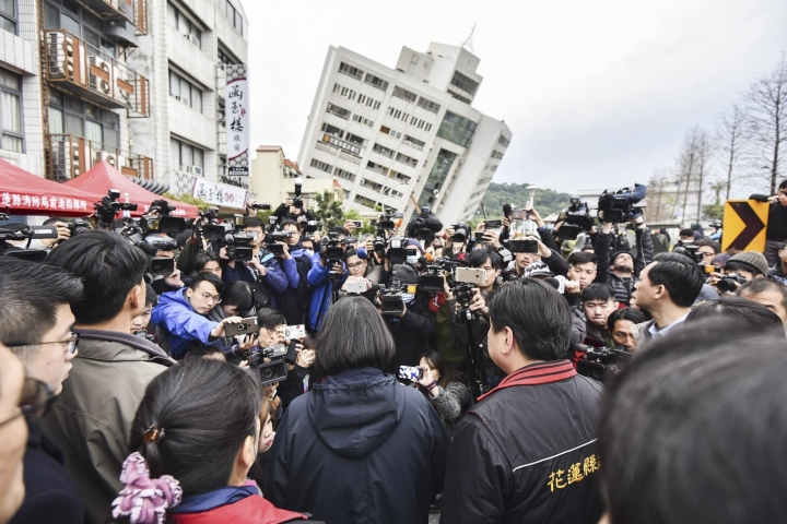 In this photo released by the Taiwan Presidential Office, Taiwan's President Tsai Ing-wen, center back-facing, is briefed at the site of a collapsed building from an earthquake, Wednesday, Feb. 7, 2018, in Hualien, southeastern Taiwan. Rescuers continue to search for dozens of unaccounted people for in several buildings damaged by a strong earthquake near the island's eastern coast. (Taiwan Presidential Office via AP)