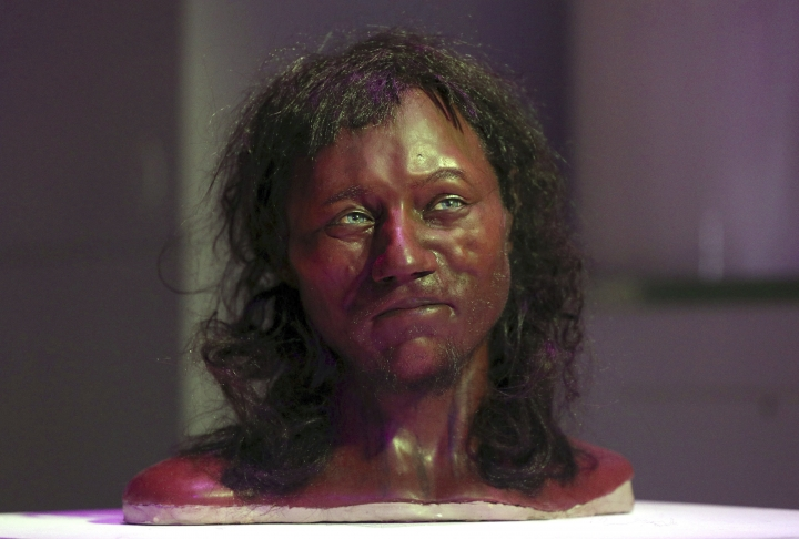 "Full facial reconstruction model of a head based on the skull of Britain's oldest complete skeleton on display during a screening event of The First Brit: Secrets Of The 10,000 Year Old Man at The Natural History Museum, in London Wednesday Feb. 7, 2018. DNA from a 10,000-year-old skeleton found in an English cave suggests he had dark skin and blue eyes. Scientists from Britain's Natural History Museum and University College London have analyzed the genome of ""Cheddar Man,"" who was found in Cheddar Gorge in southwest England in 1903. (Jonathan Brady/PA via AP)"