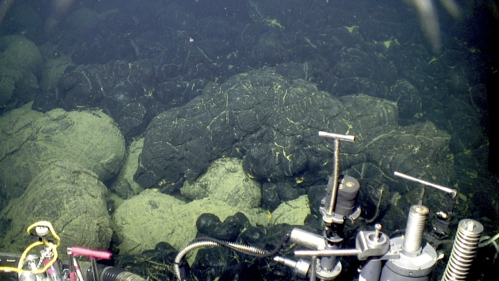 This 2015 image provided by the Woods Hole Oceanographic Institution shows the edge of the 2015 lava flow, above, at the Axial Seamount where it overlies older sedimented lavas, bottom. A study in the Wednesday, Feb. 7, 2018 journal Science Advances figures sometime after the asteroid crash creating the Chicxulub crater in the Yucatan 66 million years ago, unusual and extra strong eruptions happened on the floor of the oceans, probably the Pacific and Indian oceans. (Bill Chadwick/Oregon State University, ROV Jason, Woods Hole Oceanographic Institution via AP)