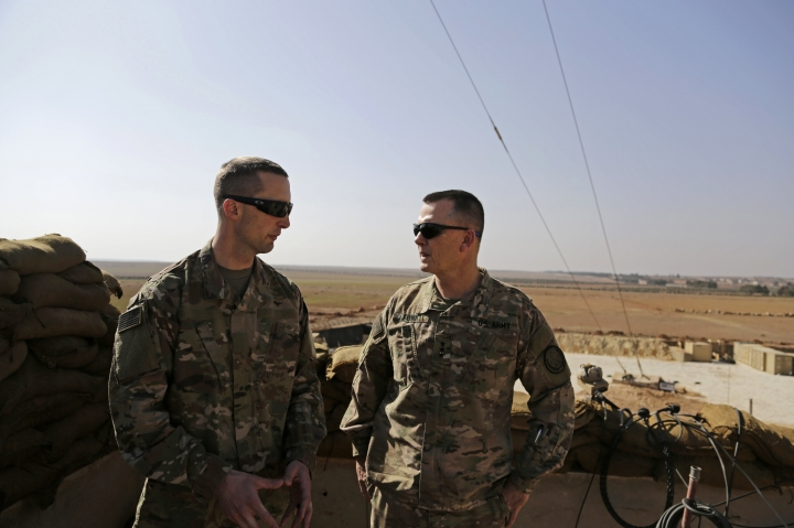 US Army Capt. Timothy Skinner, left and Lt. Gen. Paul E. Funk consult at an American outpost in the northern Kurdish town of Manbij, Syria, Wednesday, Feb. 7, 2018. Funk, the top U.S. general in the coalition fighting the Islamic State group pledged American troops would remain in the town despite Ankara's demands for a U.S. pullout. Turkey launched an offensive last month to drive Syrian Kurdish militiamen out of the enclave of Afrin and has threatened to extend its operation to Manbij. (AP Photo/Susannah George)