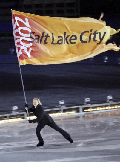 FILE--In this Feb. 8, 2002, file photo, the Salt Lake City Olympic flag is skated into the Rice-Eccles Olympic stadium during the opening ceremonies of the 2002 Winter Olympics in Salt Lake City. Salt Lake City has become the first U.S city to announce it will pursue a bid for the 2030 Winter Olympics following an announcement from an exploratory committee that studied the issue. (AP Photo/Kevork Djansezian, file)