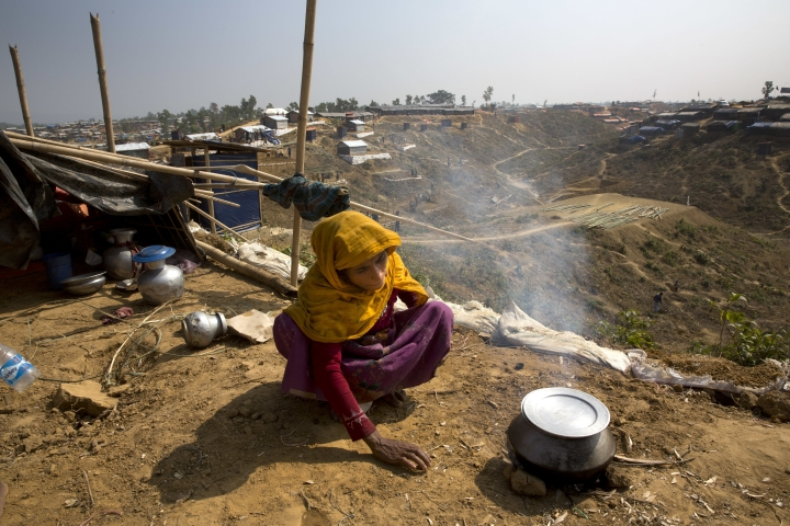 In this Saturday, Jan. 13, 2018, photo, a newly arrived Rohingya woman makes rice for her family at Balukhali refugee camp near Cox's Bazar, Bangladesh. (AP Photo/Manish Swarup)