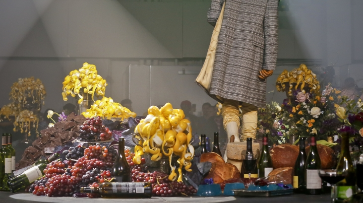 Bottles of wine and food, including grapes and chocolate, bread loaves, decorate the runway for Raf Simons men's fashion show during Fashion Week, Wednesday, Feb. 7, 2018, in New York. (AP Photo/Bebeto Matthews)