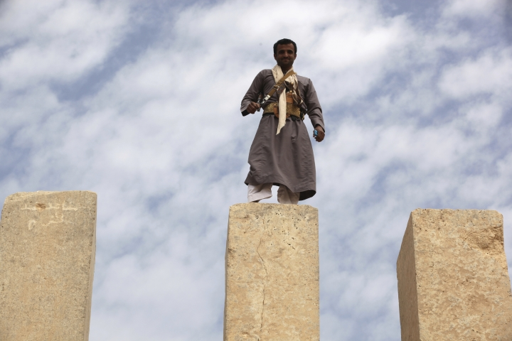 In this Saturday, Feb. 3, 2018 photo, a Yemeni militiaman stands atop a limestone column at the Awwam Temple, also known as the Mahram Bilqis, in Marib, Yemen. Experts fear the temple, as well as other historic and cultural wonders across Yemen beyond those acknowledged by international authorities, remain at risk as the country's stalemated Saudi-led war against Shiite rebels rages on. (AP Photo/Jon Gambrell)