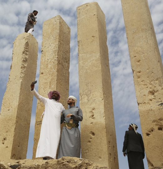 In this Saturday, Feb. 3, 2018 photo, officials take a selfie as a Yemeni militiaman stands atop a limestone column at the Awwam Temple, also known as the Mahram Bilqis, in Marib, Yemen. Experts fear the temple, as well as other historic and cultural wonders across Yemen beyond those acknowledged by international authorities, remain at risk as the country's stalemated Saudi-led war against Shiite rebels rages on. (AP Photo/Jon Gambrell)