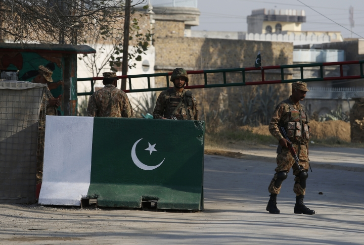Pakistani army troops stand alert at an entrance to a prison, where the trial of a university student lynching case is being held in Haripur, Pakistan, Wednesday, Feb. 7, 2018. A Pakistani court sentenced a man to death and convicted 30 others over the lynching of a 23-year-old university student who was falsely accused of blasphemy, officials said. (AP Photo/Anjum Naveed)