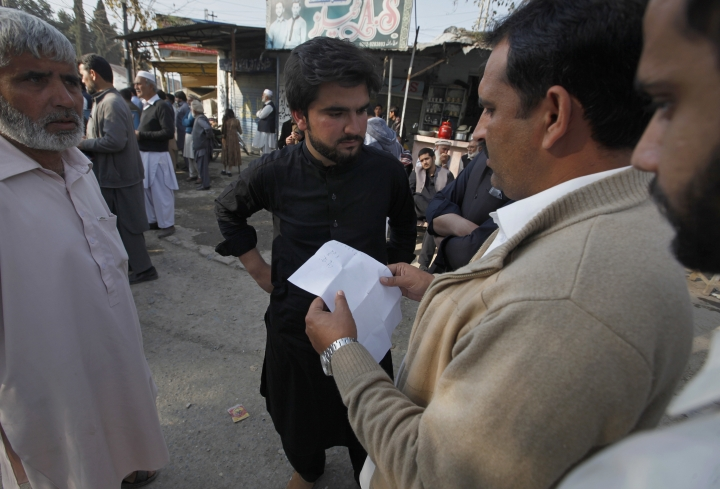 Family members and relatives of suspects in a case regarding the lynching of 23-year-old university student Mohammad Mashal Khan read from a list of those sentenced, outside a central jail during a court proceeding, in Haripur, Pakistan, Wednesday, Feb. 7, 2018. The anti-terrorism court on Wednesday sentenced a man to death and handed life sentences to five other people in connection to the lynching. Another 25 people were sentenced to four years, and 26 others were acquitted for lack of evidence. (AP Photo/Anjum Naveed)