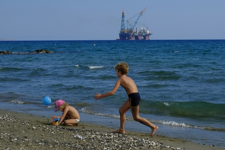 "In this photo taken on Sunday, Oct. 15, 2017 children play on a beach with a drilling platform seen in the background, on the outskirts of Larnaca port, in the eastern Mediterranean island of Cyprus. Cyprus' energy minister said that exploratory drilling off the island's southern shore has shown indications of a potentially sizeable gas deposit. Yiorgos Lakkotrypis said Thursday Feb. 8, 2018 that drilling by a consortium made up of Italy's ENI and France's TOTAL has found an ""extended column of pure natural gas"" similar in structure to a massive Egyptian field. (AP Photo/Petros Karadjias/File)"