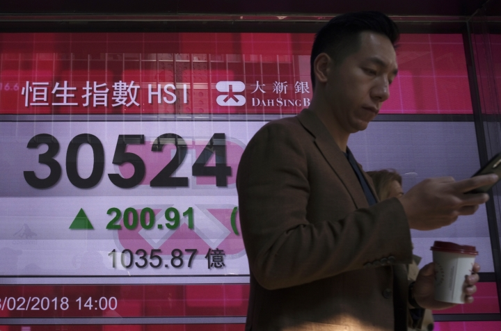 A man walks past a bank electronic board showing the Hong Kong share index at Hong Kong Stock Exchange Thursday, Feb. 8, 2018. Asian stock markets were mixed Thursday with some benchmarks erasing early morning gains. Investors remained skittish after this week's financial turmoil and overnight losses on Wall Street. (AP Photo/Vincent Yu)