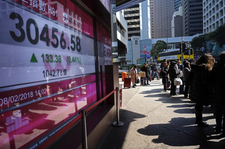 People walk past a bank electronic board showing the Hong Kong share index at Hong Kong Stock Exchange Thursday, Feb. 8, 2018. Asian stock markets were mixed Thursday with some benchmarks erasing early morning gains. Investors remained skittish after this week's financial turmoil and overnight losses on Wall Street. (AP Photo/Vincent Yu)