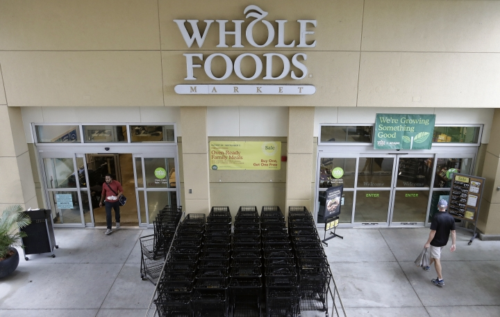 FILE- In this Aug. 28, 2017, file photo, customers shop at a Whole Foods Market in Tampa, Fla. Amazon plans to roll out two-hour delivery at the organic grocer this year to those who pay for Amazon's $99-a-year Prime membership. Amazon.com Inc. said deliveries will start Thursday, Feb. 8, 2018, in Austin, Texas; Cincinnati; Dallas; and Virginia Beach, Va. The service will expand nationwide this year. (AP Photo/Chris O'Meara, File)