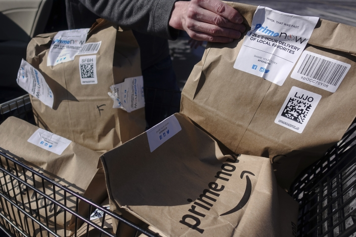 Amazon Prime Now bags full of groceries are loaded for delivery by a part-time worker outside a Whole Foods store, Thursday, Feb. 8, 2018, in Cincinnati. Amazon, which owns Whole Foods, plans to roll out two-hour delivery at the organic grocer this year to those who pay for Amazon's $99-a-year Prime membership. Amazon.com Inc. said deliveries started Thursday in Austin, Texas; Cincinnati; Dallas; and Virginia Beach, Va. (AP Photo/John Minchillo)