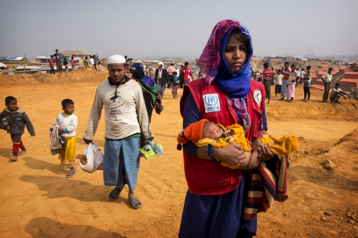 "In this Sunday, Jan. 14, 2018, photo, a volunteer carries a malnourished child from a newly arrived Rohingya family to a transit camp in the Kutupalong refugee camp near Cox's Bazar, Bangladesh. The hunger the Rohingya faced at home is evident when they come to the Bangladesh camps, where new refugees, especially children and women, suffer from ""unbelievable"" levels of malnutrition, according to Dr. Ismail Mehr. (AP Photo/Manish Swarup)"